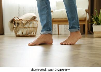 Man walking barefoot at home, closeup. Floor heating concept