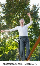 Man walking barefoot on slackline in park with arms out and deep concentrated facial expression.