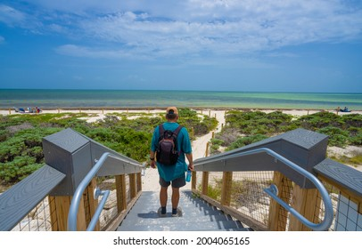 Man walking to the beach. Beautiful Florida beach with sand dunes. Bahia Honda State Park, Florida Keys, Bahia Honda Key, FLorida,USA.