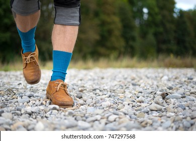 Man walking at the beach in leather shoes and blue socks. Trekking or walking outside in summer nature inspiring motivational health and fitness concept