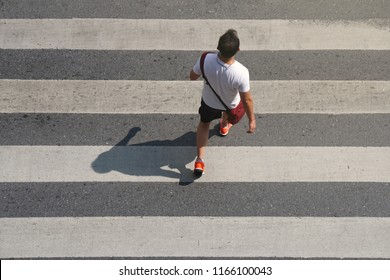 Man walking from behind with shoulder bag across the crosswalk at the junction street of city, Pedestrian safety, Top view