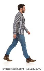 Man is walking in boots, jeans and lumberjack shirt, smiling and looking away. Side view. Full length studio shot isolated on white.