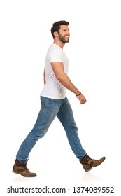 Man is walking in boots, jeans and white t-shirt, looking up and smiling. Side view. Full length studio shot isolated on white.