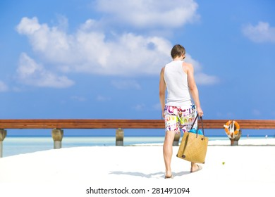 Man walking by the shore in the beach away to a jetty. He is wearing a colorful bathing suit while carrying a beach bag with towels in  it..