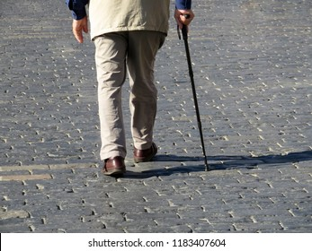 Man walking with a cane down the street. Concept for old age, diseases of the spine or joint disease, elderly people