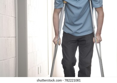 Man walking with crutches in hospiral corridor