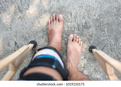 Man walking with crutches picture point of top view. injured man physical walk with crutches, shallow focus.