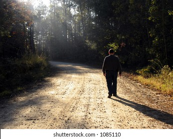 Man walking up dirt road in late afternoon with rays of sun and long shadows