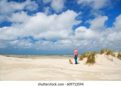 Man walking the dog at the beach