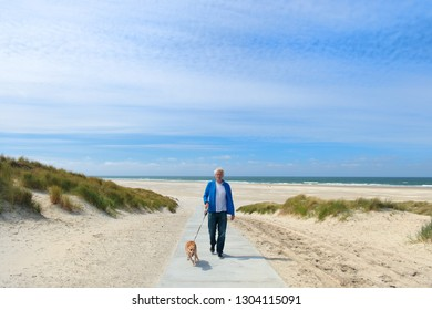 Man walking the dog at the beach at Dutch island Terschelling