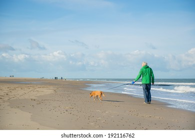 Man walking with dog at the beach in Dutch Renesse