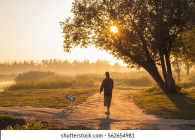 the man walking the dog early in the morning by the river, copy space