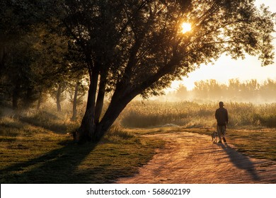 the man walking the dog early in the morning by the river