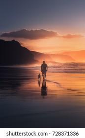 man walking the dog on beach at sunset
