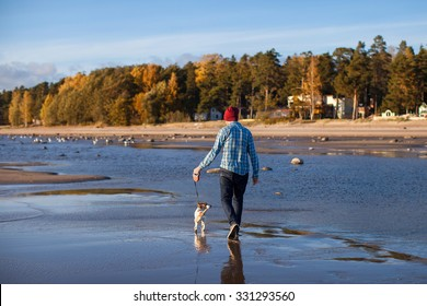 man walking with a dog on the shoreline spit on the background of the autumn woods