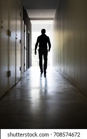 Man walking down a corridor towards a well lit end/exit