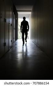 Man walking down a dark corridor towards a well lit end/exit