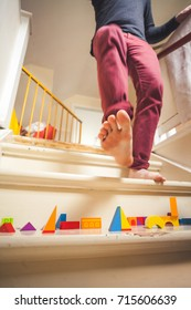 Man walking down staircase filled with children's toys