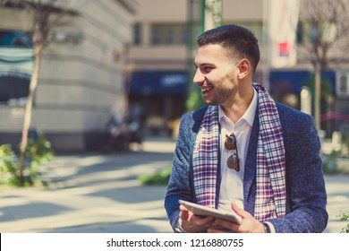 A man is walking down the street with a smile on his face, holding his tablet and enjoying the view of the city