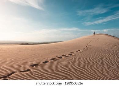 Man walking dry desert alone with footprints behind, nobody around, Mui Ne, Vietnam