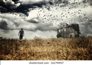 Man walking in a field towards a haunted house
