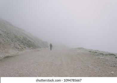 Man walking in the fog. Misty dirt road in mountains