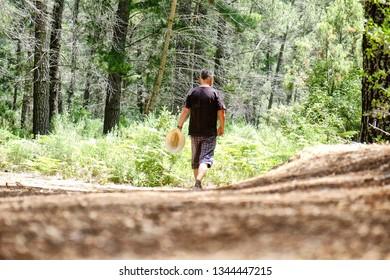 A man walking in a forest in Cruz de Juanar in Spain