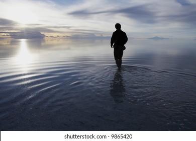 a man walking in to heaven in a uyuni salt lake bolivia