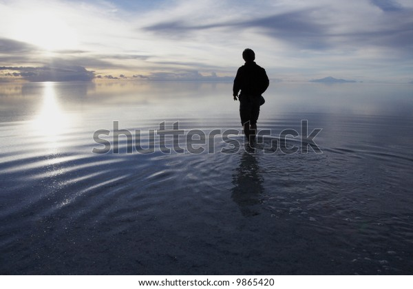 a man walking in to heaven in a uyuni salt lake bolivia