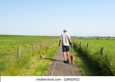 man walking his dog in agricultural landscape