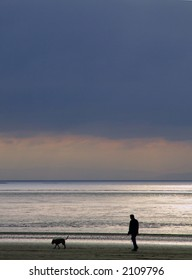 man walking his dog on the beach at sunset