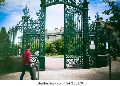 Man walking into Jardin Lecoq park in Clermont Ferrand, France, Auvergne Region