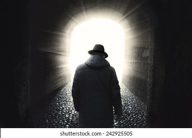 Man walking into light
