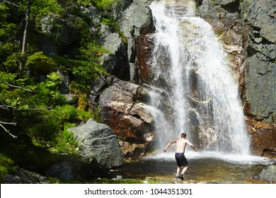 Man walking into the mountains waterfall alone to take a bath there. Travel Lifestyle adventure concept of an active vacations into the wild nature.