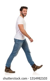 Man is walking in jeans and white t-shirt, looking at camera and smiling. Side view. Full length studio shot isolated on white.