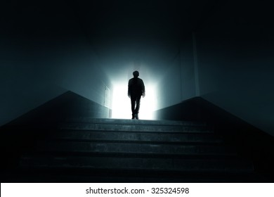 Man walking to the light in the dark tunnel.