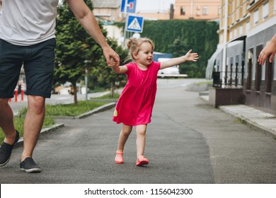 Man walking with little girl in the street