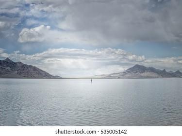 A man walking in the middle of the water far away. Bonneville Salt Flat, Utah