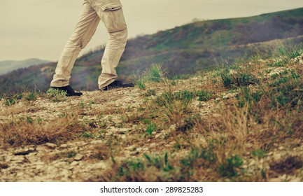 Man walking in the mountains, view of legs