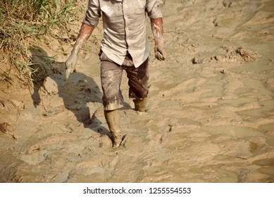 Man walking in the muddy area to catch fish unique photo