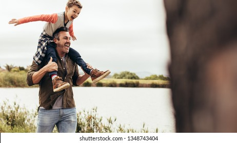 Man walking near a lake with his son sitting on his shoulders. Father and son having fun together enjoying near a lake.