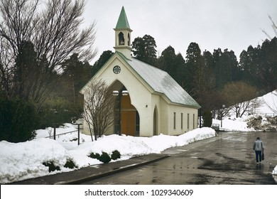 A man walking next to a chapel in a cloudy day in winter