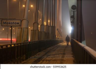 Man walking in the night through bridge