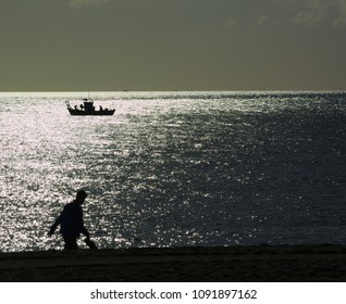 A man walking on a beach and a fishing boat out at sea silhouetted.