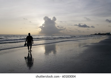 Man walking on the beach with an interesting cloud in the sky.