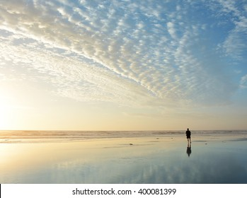 Man walking on beach at sunrise, beautiful cloudy sky reflected on the beach, Jacksonville, Florida, USA.