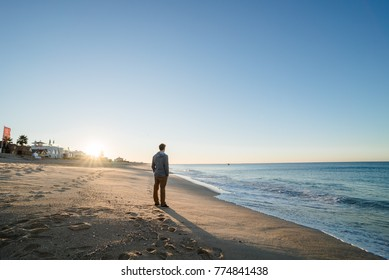 Man walking on the beach at sunrise in Portugal
