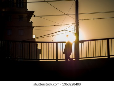 Man walking on the bridge into the sun early in the morning
