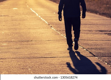 Man walking on a concrete in evening at sunset light