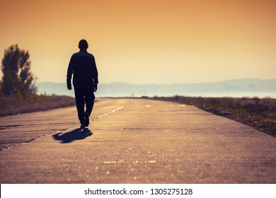 A man walking on the concrete road along the sea at golden sunset and looking to mountain